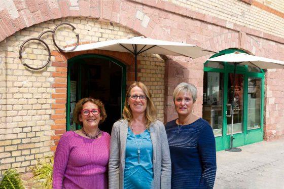 Drei Mitarbeiter vor dem Laden